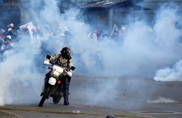 A riot security forces member rides his motorcycle as demonstrators clash with riot security forces while rallying against Venezuela's President Nicolas Maduro in Caracas
