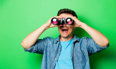 Young smiling man with binocular