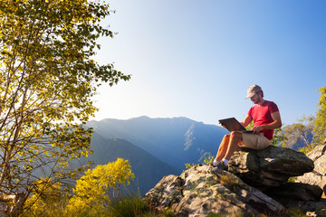 Young caucasian man sitting outdoor on a rock working on a laptop pc in mountain area.