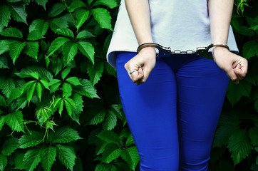 Fragment of a young criminal girl's body with hands in handcuffs against a green blossoming ivy leaves background. The concept of detaining an offender of a female criminal in a rural environment