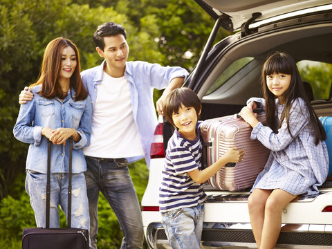 asian family traveling by car