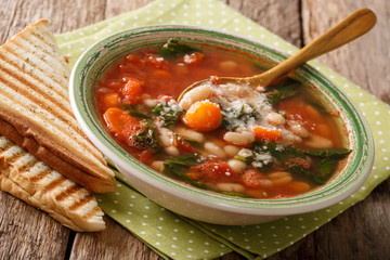 Italian soup with white beans, tomatoes, spinach, carrots and parmesan close-up. horizontal