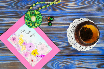 """Ceramic bowl piala cup with green tea with jasmine and picture card with inscription """"One fine day"""", green pendant made from a seed bead and earrings on blue boards. Top view. Happiness Still life"""