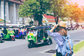 Young woman traveler with sky blue backpack and hat looking the way with tuk tuk thailand background from wat pho at Bangkok Thailand