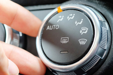 hand on air positioner control in car dashboard. Car air conditioning