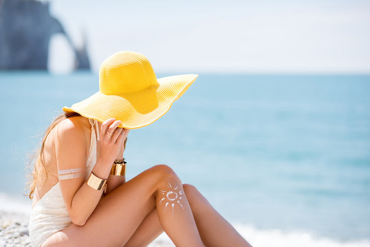 Beautiful woman in yellow hat sunbathing with sunscreen UV protective lotion on the beach