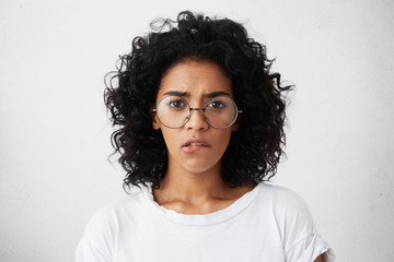 Headshot of African pretty female with dark eyes, well-marked eyebrows and bushy curly hairstyle wearing big round glasses and white T-shirt biting her lip while having self-confidence and doubt