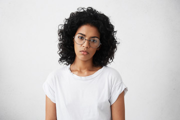 Serious and sad black woman with Afro haircut wearing big elegant glasses and casual clothes posing in studio over white background having thoughtful expression. People, lifestyle, emotions concept