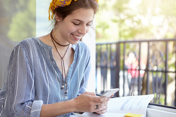 Young housewife casually dressed sitting outdoors at balcony holding smartphone being happy to recieve message having good day and rest reading book having free time. Cute female with cell phone