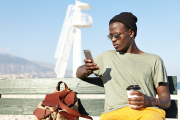 Young attractive dark-skinned male wearing black hat, casual T-shirt and yellow trousers sitting at bench near marine landscape reading news online, browsing pictures and drinking delicious coffee
