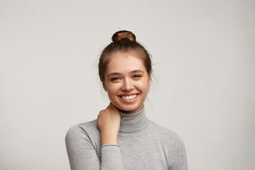 Indoor portrait of cute young European female with charming cute smile, rubbing her neck, feeling a bit uncomfortable while talking to handsome male, posing isolated against grey wall background