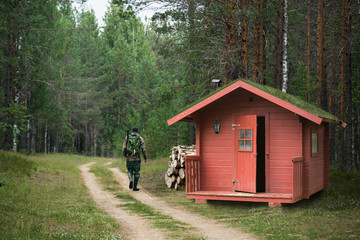 Fotorollo Jagd Hunter with a gun went hunting from a red lodge with grass on the roof and walks along the forest road