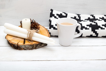 hygge. A cup of hot chocolate and a blanket is on a wooden table