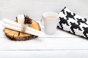A cup of hot chocolate, a blanket, candles - items for a cozy holiday