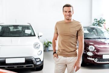 Happy man standing in automobile showroom