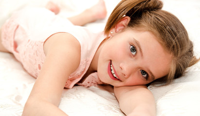Adorable smiling little girl is resting on a bed