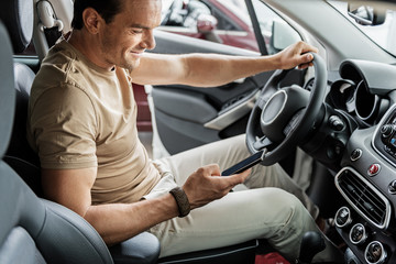 Outgoing male watching at phone in car