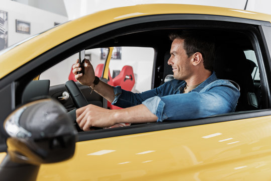 Outgoing man looking at phone in car