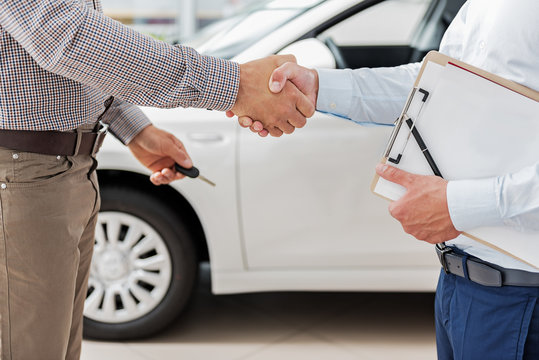 Salesman and buyer joining arms near automobile