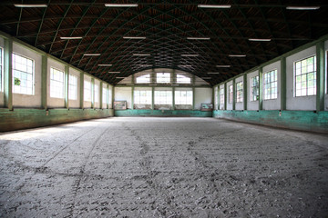 Panoramic view of an old fashioned riding hall with sandy covering without people