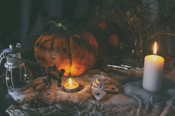 Halloween home decorations with candles, spiders, pumpkin, cookies and jar for treat and black berries. Dark background. Shallow depth of field. Toned