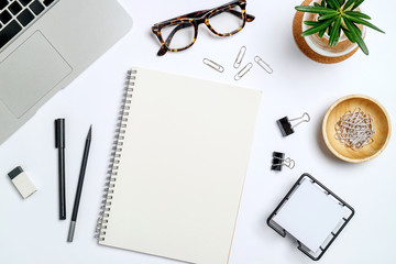 Top view workspace mockup on wood table with notebook, pen, glasses, clips and accessories.