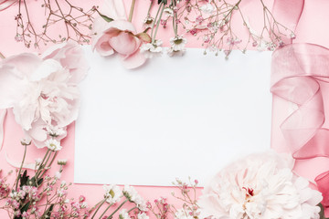 White blank card with pastel flowers and ribbon on pink pale background, floral frame. Creative greeting, Invitation and holiday concept