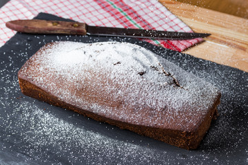 Homemade baked sweet gingerbread on a black slate plate.