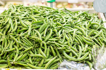 Green pea pods at market as a background. Selective focus