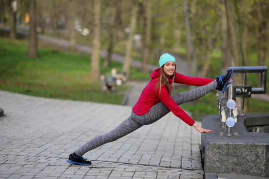 Smiling woman stretching in a twine in the park, sport, healthy lifestyle