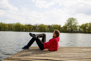 Woman resting on pier near river, healthy lifestyle
