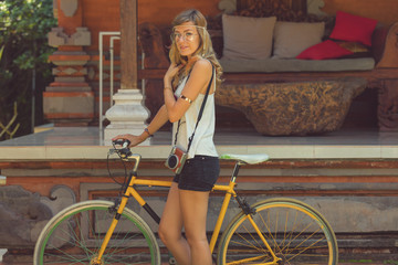 Attractive cute girl standing with old bicycle.