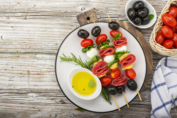 Healthy snack: mouth-watering kebabs on a picnic with tomatoes, mozzarella, salami, black olives, Basil, tortellini pasta on a cutting Board on wooden background with olive oil and herbs. From the top