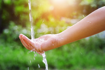 Water pouring splash in hand and nature background