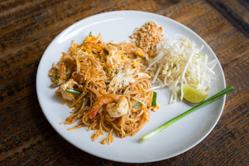 Thai Fried Noodles in white dish on wooden table