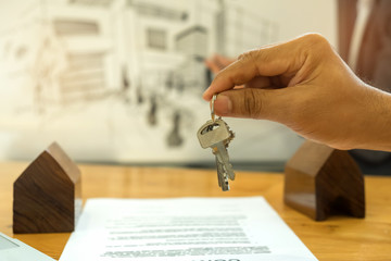 Real estate concept,Sales are selling home,holds the house key in hand with house model.