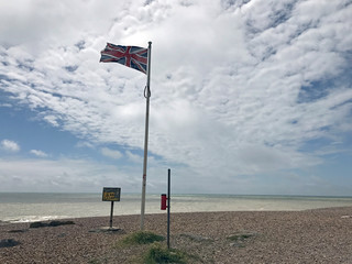 Britain's national flag, known as the Union Jack, is seen by a sign that used to read 'Danger Keep Off' on the coastline in Worthing