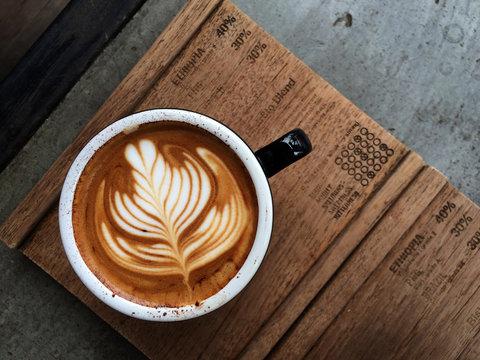 Nice Texture of Latte art on hot latte coffee . Milk foam in heart shape leaf tree on top of latte art from professional barista artist