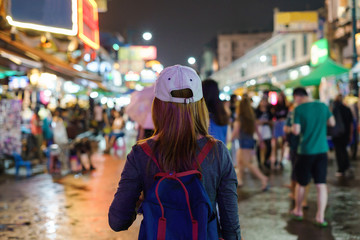 young woman traveler walking in the Khao San road at night