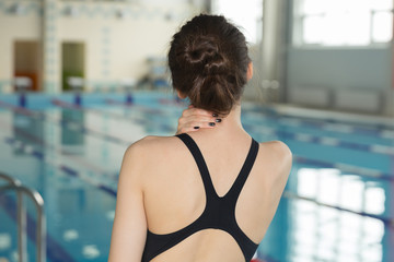 swimmer girl with neck pain before swimming moment standing near poolside