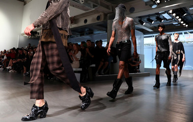 Models present creations at the KTZ catwalk show at London Fashion Week Men's in London