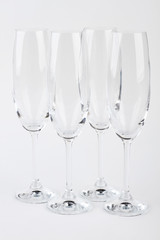 Four fragile champagne glasses isolated. Luxury beverage from crystal flutes.