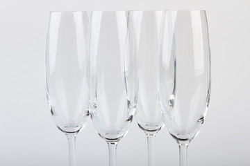 Closeup four champagne goblets. Set of wineglasses, white background. Tableware for company.