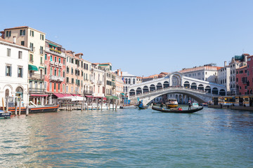 View of Rialto Bridge , Venice , Veneto, Italy from the Grand Canal with a gondola passing in front of it and reflections