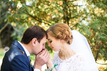 Bride and groom in a park kissing. couple newlyweds bride and groom at a wedding in nature green forest are kissing photo. Wedding Couple