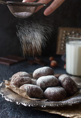 Homemade chocolate crinkles in powdered sugar on vintage plate and a glass of milk on dark stone background. Chocolate cookies with cracks, delicious dessert, selective focus