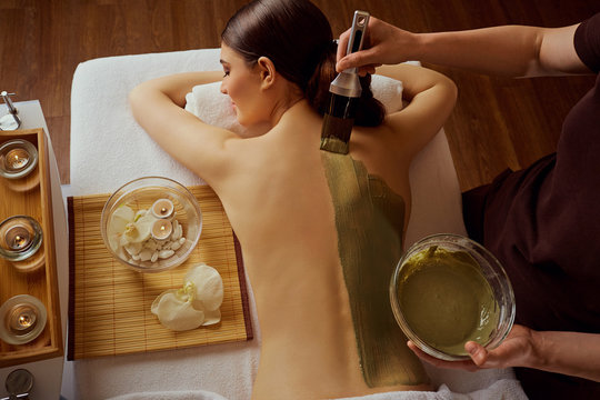 Young woman is put on a mask on her back in  spa salon.