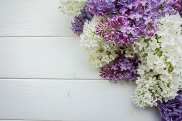 Branch of lilac on a white-painted wooden boards. Top view. Design element for card, banners, print.