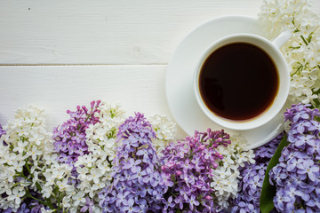 Background with branches of lilac in different colors - white, lilac and purple on a white-painted wooden boards and a Cup of black coffee Top view Copy space The theme of spring, summer, good morning