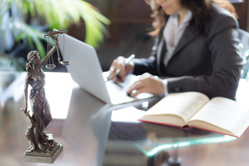 Lawyer office. Statue of Justice with scales and lawyer working on a laptop. Legal law, advice and justice concept